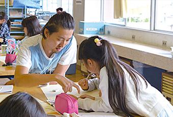 桃川小学校の図工授業で子どもたちにアドバイスするアーティストの中島佑太さん(左)=2017年10月場